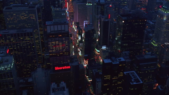 vidéos et rushes de aerial over skyscrapers in theatre district and times square at night / down seventh avenue towards lower manhattan / view of empire state building / new york city - billboard