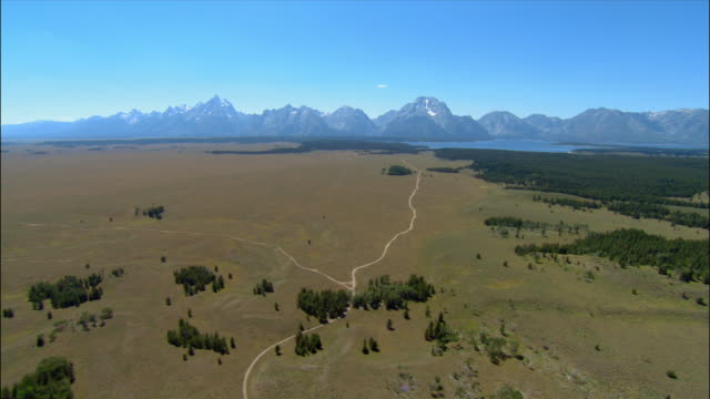 Aerial over small dirt road approaching Grand Tetons and Jackson Lake/ Wyoming