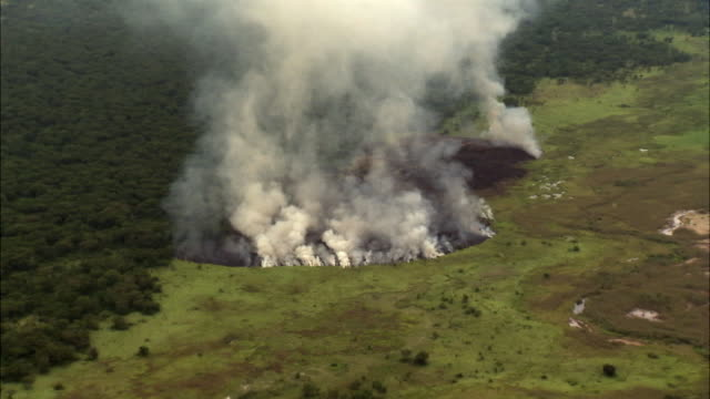 aerial over smoke and wild fire, uganda - smoke physical structure stock videos & royalty-free footage