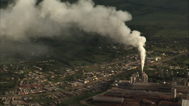 aerial over smoking factory, uganda - chimney stock videos & royalty-free footage