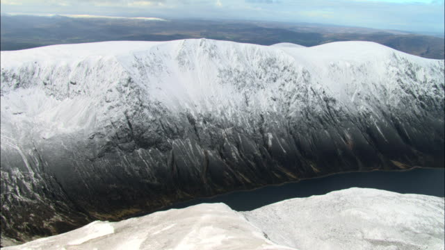 Aerial over snow covered mountains and loch, Cairngorms, Scotland