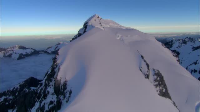 Aerial over snowy mountain ridge above cloudline/ Fiordland National Park, New Zealand
