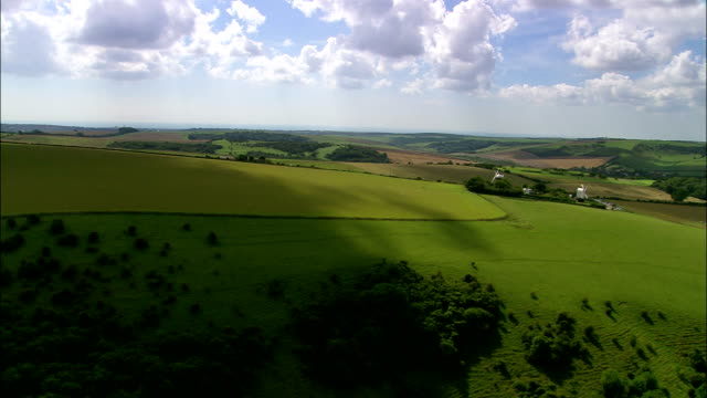 vidéos et rushes de aerial over south downs landscape to jack and jill windmills / clayton, west sussex, england - patchwork landscape