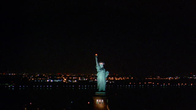 Aerial over Statue of Liberty and New York Harbor at night