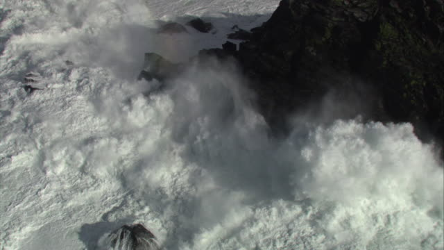 aerial over stormy sea crashing against cliff, cornwall, uk - cliff stock videos & royalty-free footage