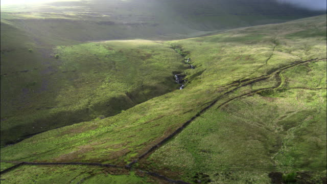 Aerial over stream and Brecon hills, Wales, UK