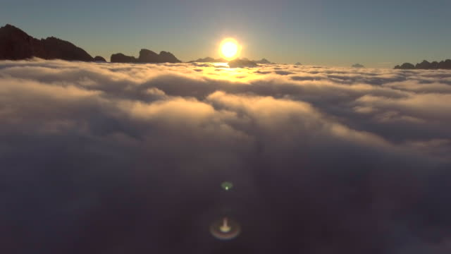 Aerial: over the high mountains in beautiful clouds