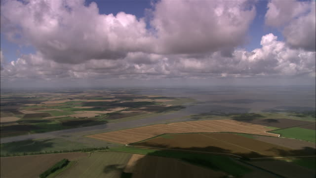 aerial over the wash and the fens with cumulus clouds in sky / lincolnshire, england - lincolnshire stock videos & royalty-free footage