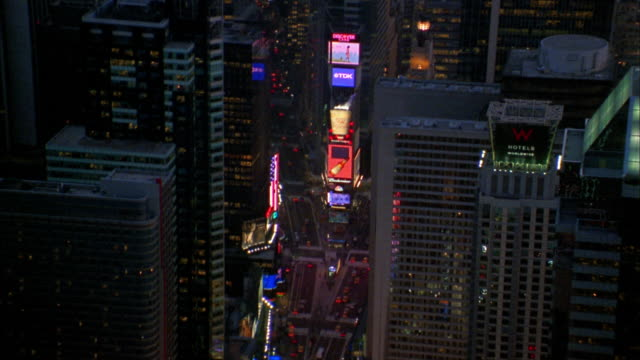 Aerial over Times Square and building rooftops at night