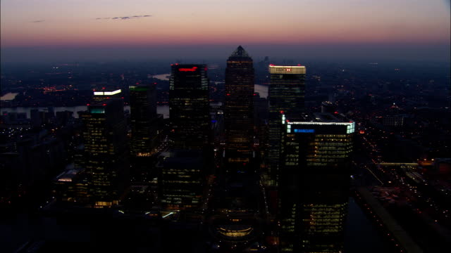Aerial over tops of skyscrapers in Canary Wharf at dusk / London