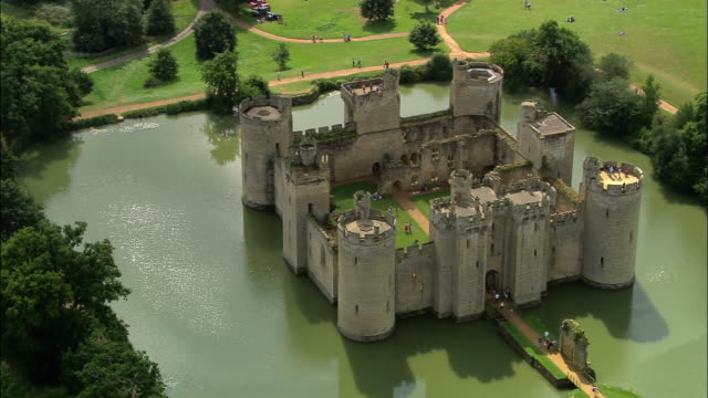 Aerial over tourists entering Bodiam Castle surrounded by moat / East Sussex, England