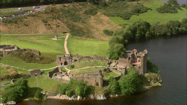 Aerial over tourists visiting Urquhart Castle / revealing Loch Ness in background / Highland, Scotland