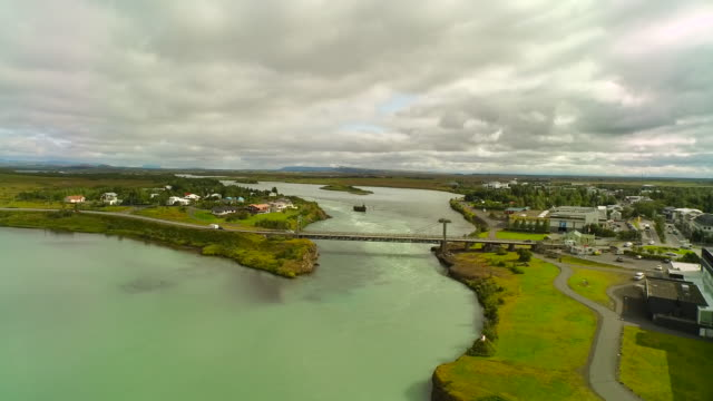 Aerial over town in Iceland, over river and bridge