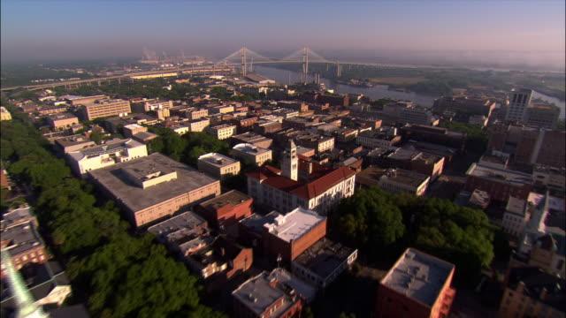 Aerial over town toward Talmadge Bridge/ waterfront area and Savannah River/ over bridge toward industrial area/ Savannah, Georgia
