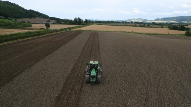 aerial over tractor towing roller in ploughed field, uk - tractor stock videos & royalty-free footage