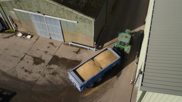 aerial over tractor towing wheat grain on farm, uk - barn stock videos & royalty-free footage