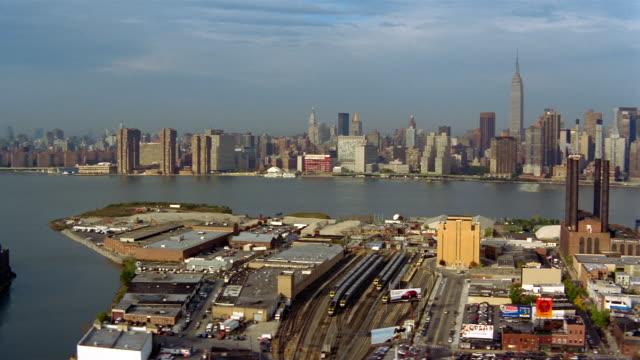 vidéos et rushes de aerial over train yards with new york city skyline in background / long island city, queens, new york - reine monarque