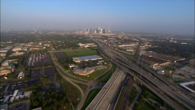 stockvideo's en b-roll-footage met aerial over trees approaching city/ warehouses and motorways with traffic/ into cityscape and over skyscrapers/ houston, texas - toyota motor