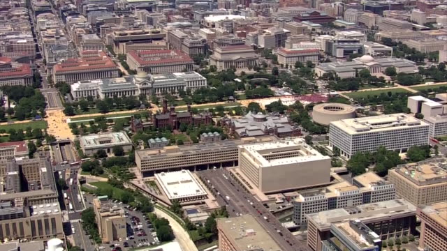 aerial over washington dc, over the j. edgar hoover, fbi building and zooming out to reveal the smithsonian castle, the museum of natural history and... - スミソニアン協会点の映像素材/bロール
