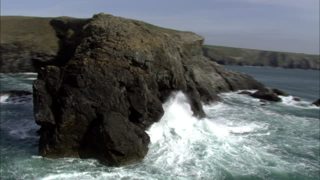 Aerial over waves crashing against headland, Cornwall, UK
