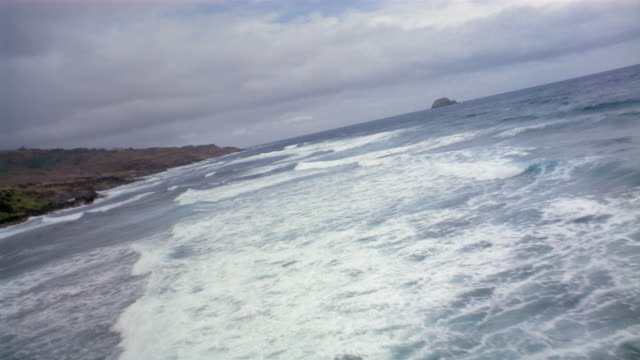 vidéos et rushes de aerial over waves in the pacific ocean off rocky coastline / southern california - océan pacifique nord