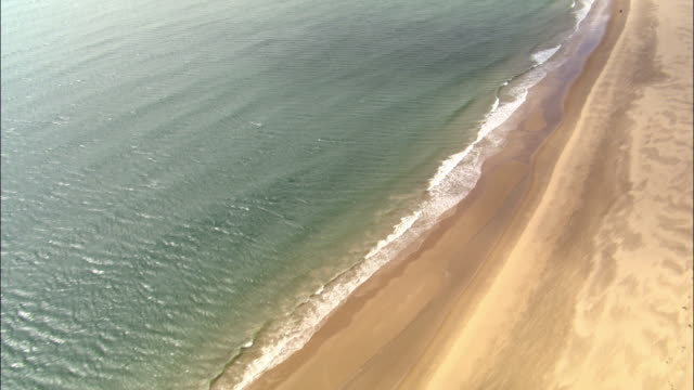 aerial over waves lapping onto beach, dorset, uk - beach stock videos & royalty-free footage