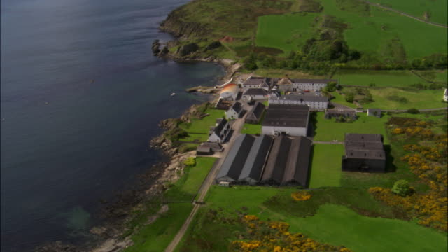 aerial over whisky distillery on coast of islay, scotland, uk - scotland stock videos & royalty-free footage