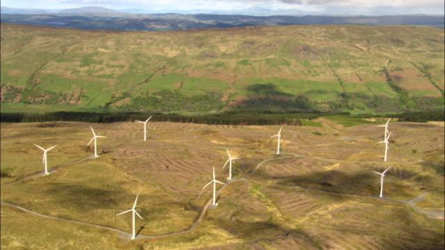 aerial over wind turbines on hill, scotland, uk - wind turbine stock videos & royalty-free footage