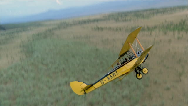 aerial overhead side view of biplane flying over planes / pulling up and turning - propeller stock videos & royalty-free footage