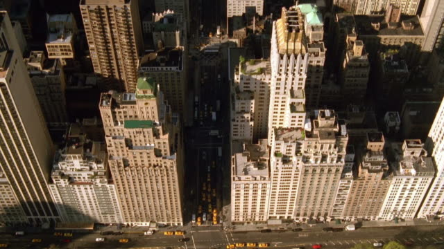 Aerial overhead wide shot Central Park South moving south over skyscrapers on Sixth Avenue / NYC