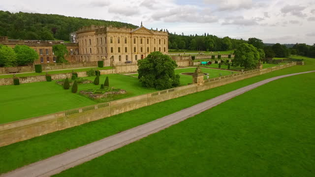 aerial pan: a stunning sandstone stately home surrounded by picturesque grounds and lush forests - chatsworth, united kingdom - boundary stock videos & royalty-free footage