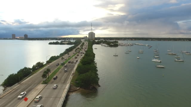 aerial pan across causeway in miami over the bay during sunset - causeway stock videos & royalty-free footage