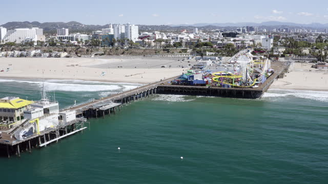 aerial pan: amusement pier crosses wide sandy beach to surf by city stretching to hills in sun - santa monica, california - wide stock videos & royalty-free footage