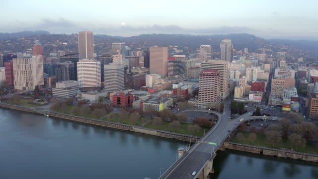 aerial pan: bank of columbia river and cityscape with tall skyscrapers and forested hills in sunshine - portland, oregon - portland oregon点の映像素材/bロール