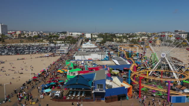 aerial pan: crowded santa monica pier on sunny day - santa monica, california - santa monica pier stock videos & royalty-free footage