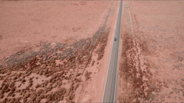 Aerial Pan Down: Cars Driving Down Road In Middle Of Desert Plain in Monument Valley, UT