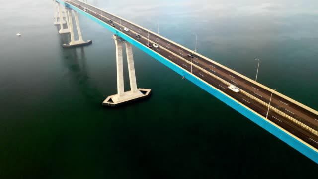 aerial pan down: long bustling bridge over dark green ocean water in san diego, united states of america - coastal feature stock videos & royalty-free footage