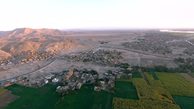 aerial pan from gurneh village and deir el-bahari on the west bank of the nile opposite luxor. - land stock videos & royalty-free footage