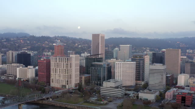 aerial pan: full moon over stunning cityscape with tall skyscrapers and forested hills - portland, oregon - portland oregon stock videos & royalty-free footage