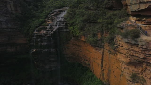 aerial pan: hiking on cliff wall next to beautiful waterfall, blue mountains, australia - cliff stock videos & royalty-free footage
