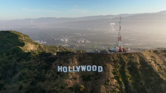 aerial pan: hollywood sign and mount lee on sunny day with backdrop of north la - hollywood, california - santa monica sign stock videos & royalty-free footage