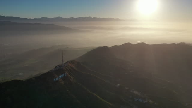 vidéos et rushes de aerial pan: hollywood sign and santa monica mountain range at sunset with view towards pasadena - hollywood, california - hollywood california
