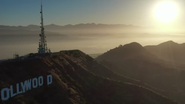 aerial pan: hollywood sign and the santa monica mountain range at sunset - hollywood, california - hollywood california stock videos & royalty-free footage