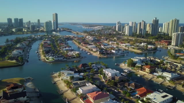aerial pan: incredible canal frontage homes with pontoons and gold coast skyline, gold coast, australia - canal stock videos & royalty-free footage