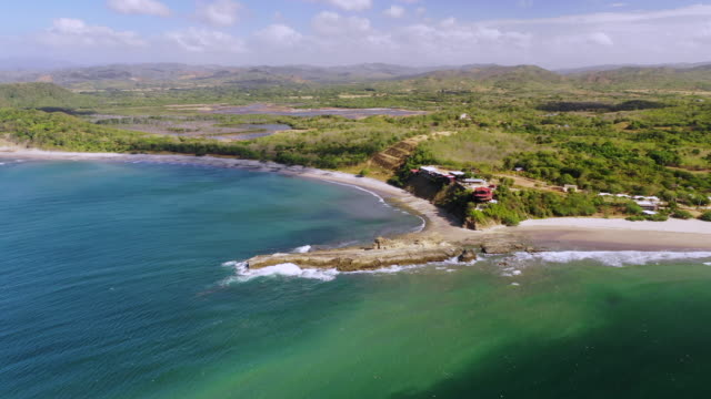 aerial pan left: green forest covering plain and hills by rocky ocean shore - el gigante, nicaragua - ニカラグア点の映像素材/bロール