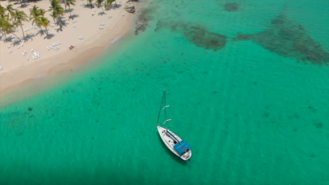 aerial pan left to right: clear waters of the cocuyo beach with boat docked - hispaniola stock videos & royalty-free footage