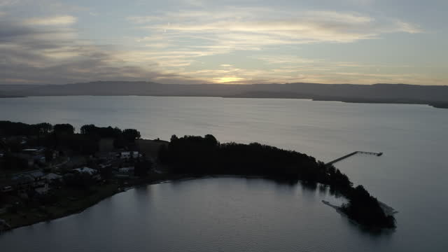 aerial pan left to right: homes by the big lake in the dark - wollongong, australia - lake stock videos & royalty-free footage