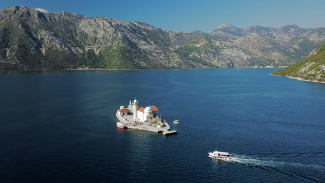 aerial pan left to right: lake of perast with boats passing the lighthouse - perast stock videos and b-roll footage