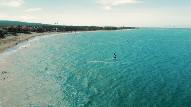 aerial pan left to right: para surfing and windsurfing in the beach of cabarete - hispaniola stock videos & royalty-free footage