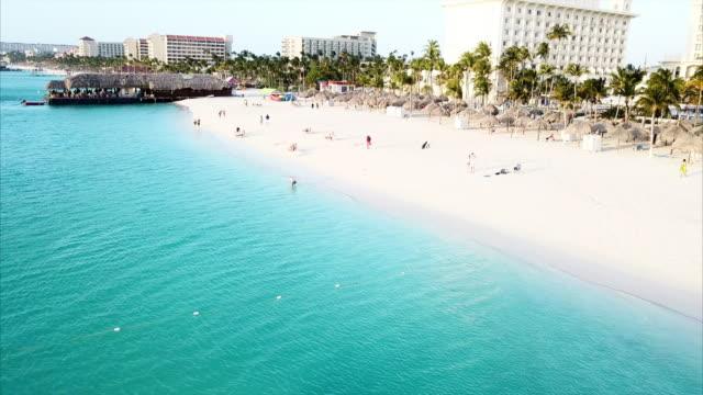 aerial pan left to right: people enjoying the beach of oranjestad aruba in oranjestad, aruba - tourist resort stock videos & royalty-free footage